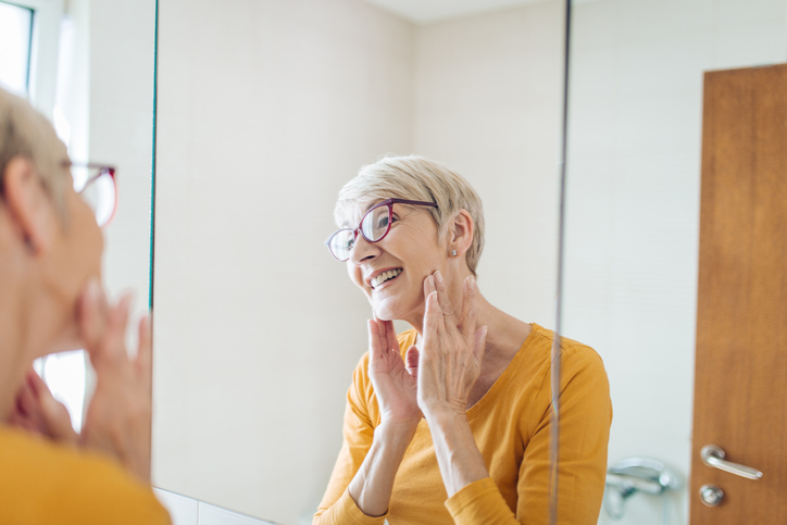 senior woman practicing face yoga in the mirror