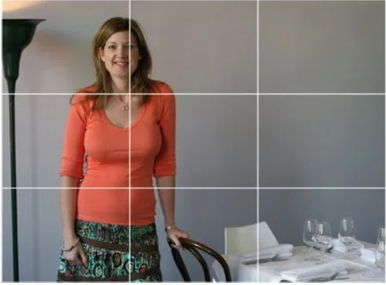 An image of a woman standing next to a table with lines added to the image to demonstrate the rule of thirds.