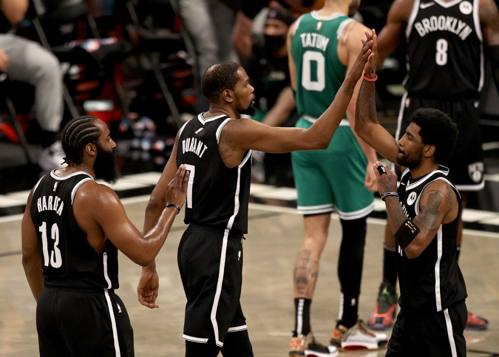 Kevin Durant and James Harden of the Brooklyn Nets congratulate teammate Kyrie Irving.